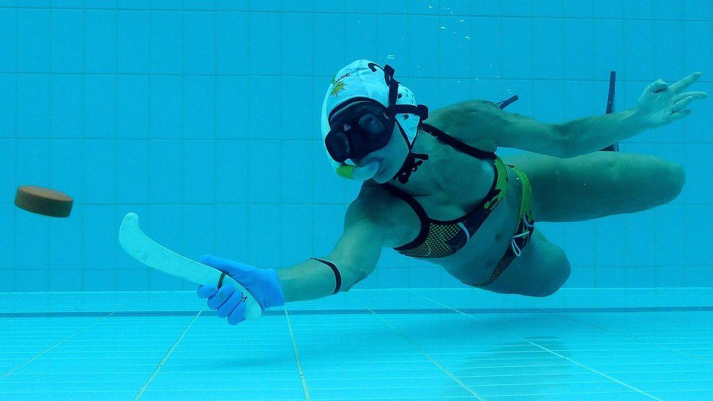 Удар по шайбе в подводном хоккее.