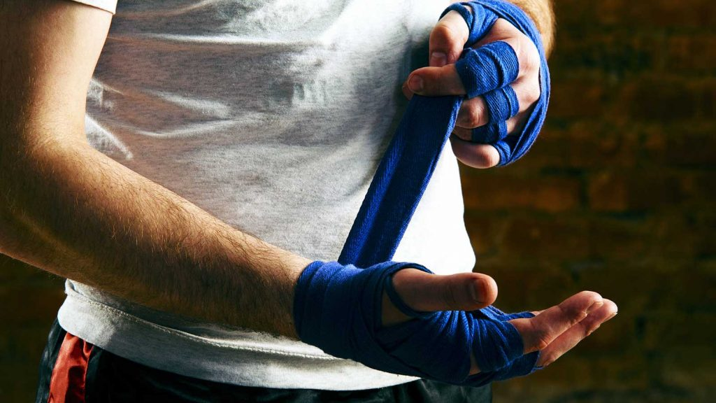 Боксёр наматывает бинты.